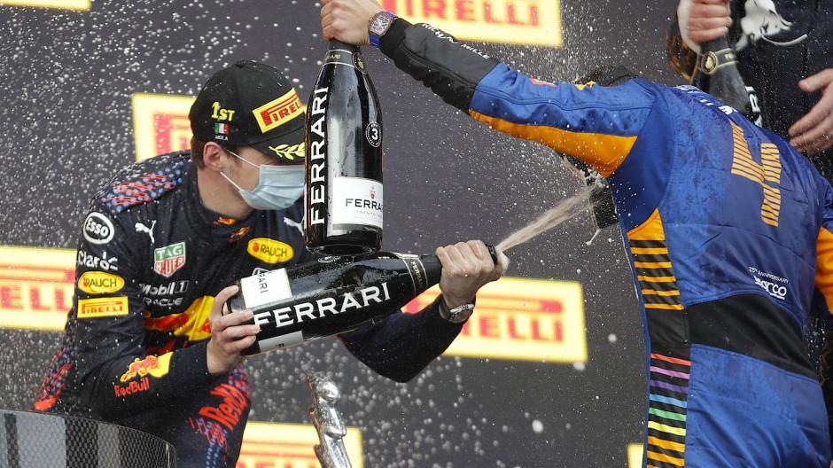 Formel-1-Sieger Max Verstappen (l.) und der Drittplatzierte Lando Norris feiern mit Ferrari-Sekt auf dem Siegerpodest.