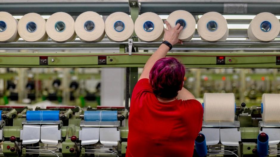 Eine Frau arbeitet an einer Maschine für Textiltechnik. Auch diese Branche hat stark mit Umsatzeinbußen zu kämpfen.
