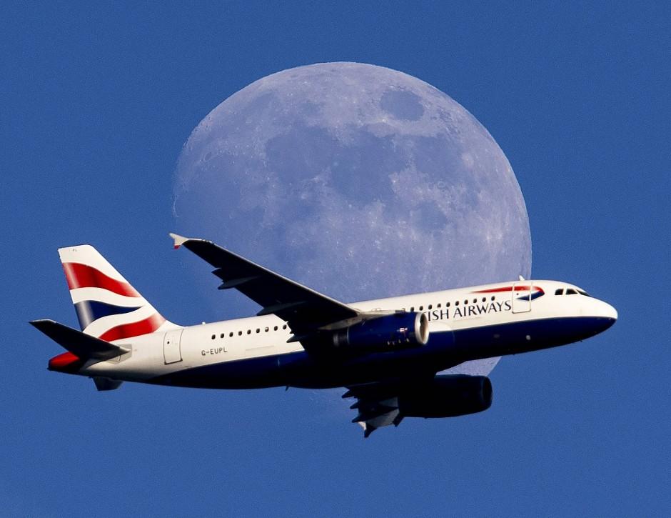 Der Mond geht auf, als ein Flugzeug von British Airways zum Frankfurter Flughafen fliegt.