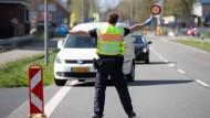 Ein Beamter der Bundespolizei winkt in Niedersachsen an der Grenze zu den Niederlanden ein Auto heraus.