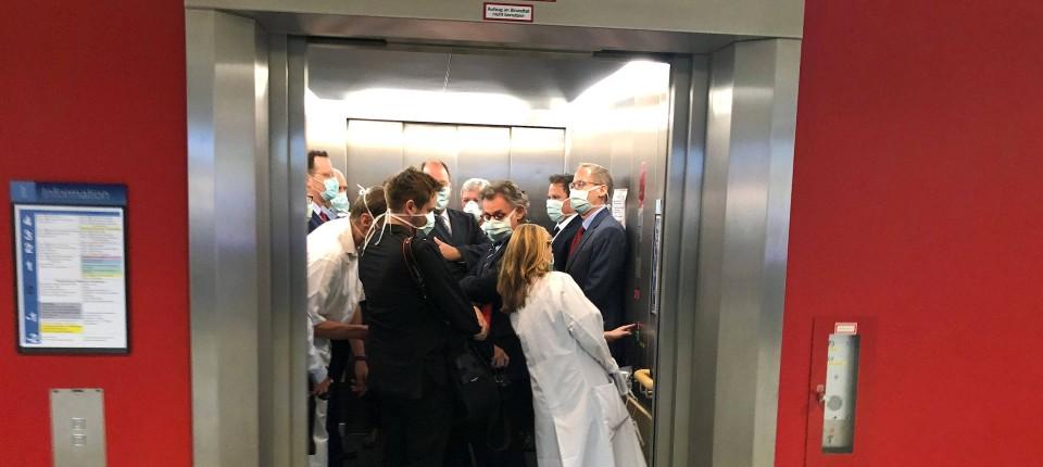Mediziner und ranghohe Politiker in einem vollen Fahrstuhl am vergangenen Dienstag