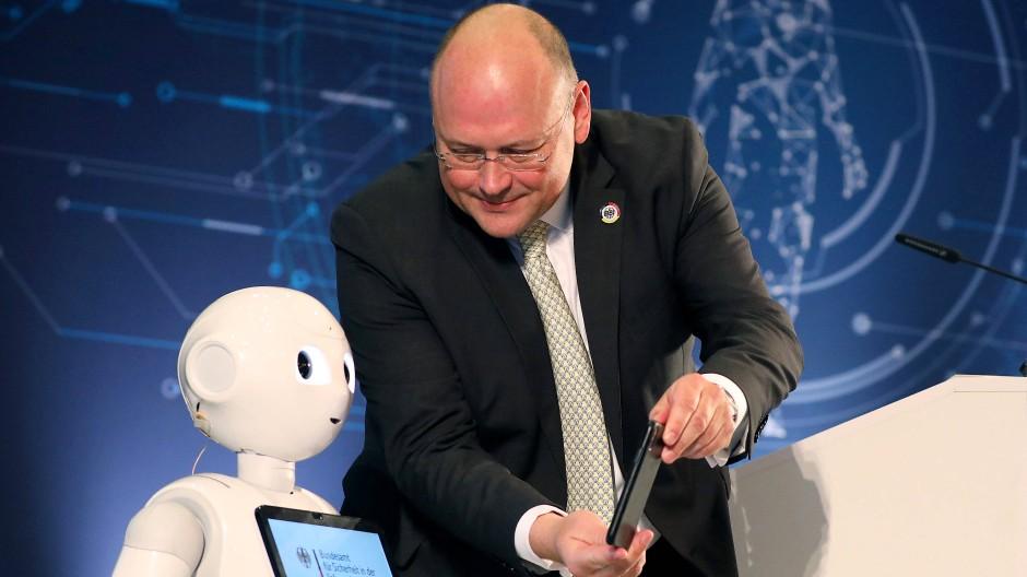 """Arne Schönbohm, Präsident des Bundesamtes für Sicherheit in der Informationstechnik (BSI), zeigt dem Roboter """"Pepper"""" ein Selfie"""