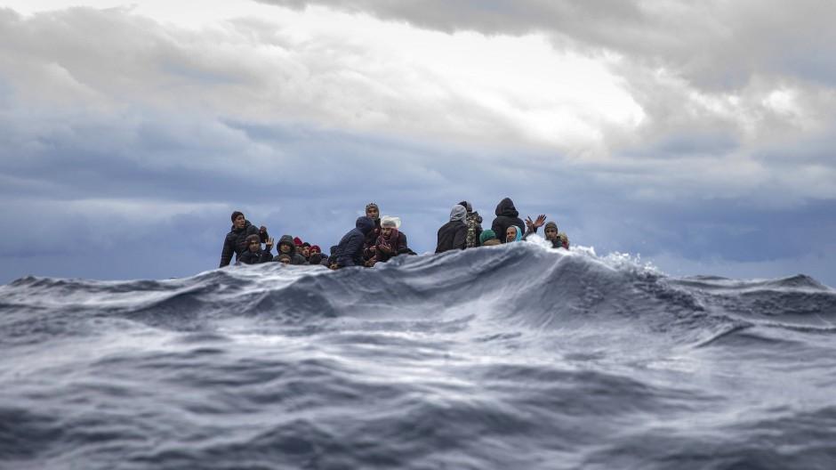Männer aus Marokko und Bangladesch warten in einem Holzboot vor der libyschen Küste auf Rettung.