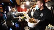 """Auf dem Tresen in der Kneipe """"Elbschlosskeller"""" in Hamburg bereiten Helfer und Helferinnen Suppe, Brote und andere Lebensmittel für Obdachlose und Bedürftige vor."""