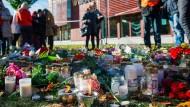 Vor der Schule in Trollhättan legen Menschen im Gedenken an die Opfer Blumen nieder.