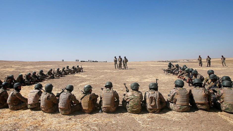 Kämpfer der sunnitisch dominierten arabischen Truppen vor Mossul sitzen in Bashiqa bei einer Übung zusammen