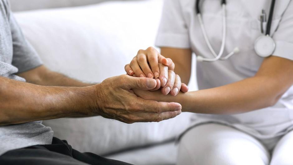 Sensibler Umgang: eine Pflegekraft beim Patientengespräch.