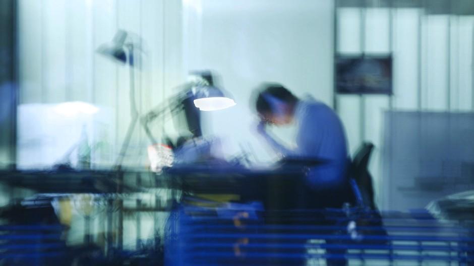 Ein Mann arbeitet am späten Abend noch an seinem Schreibtisch in einem Büro (Symbolbild).