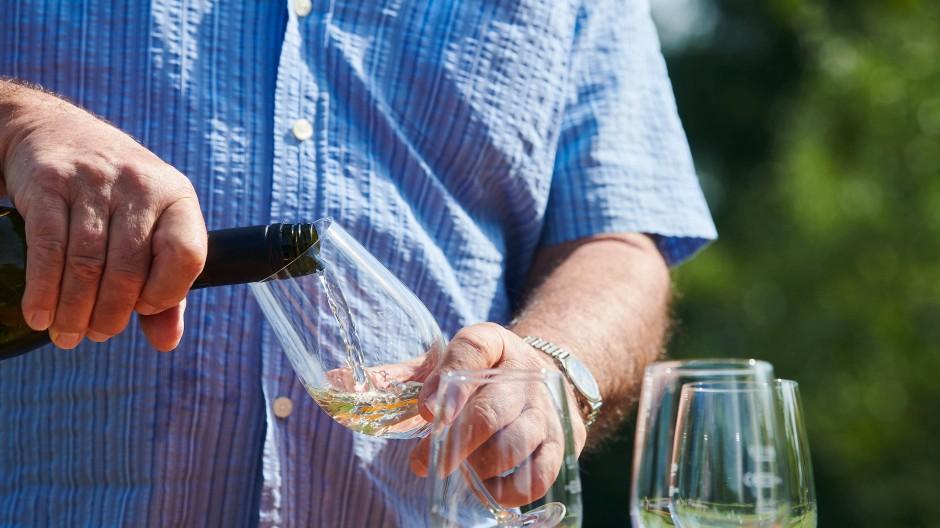 Ein Mann schenkt seinen Gästen und sich Wein ein (Symbolbild).
