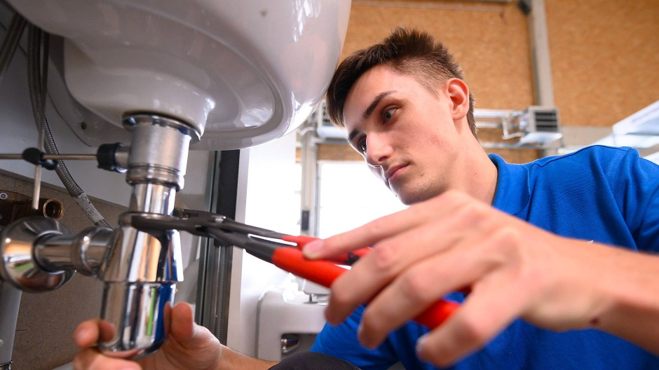 Ein Auszubildender übt mit einer Rohrzange an einem Waschbecken.