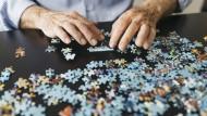 Ein Rentner macht ein Puzzle