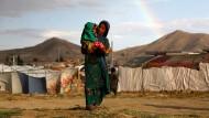 Ein afghanisches Mädchen trägt ein Kind auf dem Arm in einem Flüchtlingscamp außerhalb Kabuls, Juni 2019.