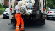 Ein Mitarbeiter der Abfallwirtschaft Region Hannover wirft gelbe Säcke in einen Müllwagen (Symbolbild).