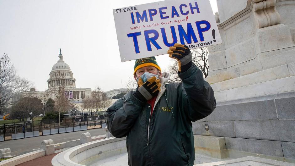 Ein Demonstrant hält ein Schild in der Nähe des Kapitols, auf dem Impeach Trump! steht.