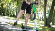 Ein Teilnehmer beim Fahrsicherheitstraining für Elektro-Tretroller übt auf einem Verkehrsübungsplatz das Anzeigen des Richtungswechsels mit dem gestreckten Bein.