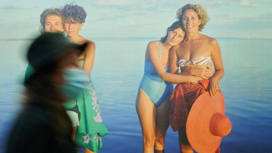 """Adieu, Idyll am Meer: Besucherin mit Mund-Nasen-Schutz am Donnerstag in der Ausstellung """"America 1970s/80s"""" in Berlin vor einem Werk von Joel Meyerowitz."""