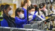 Mitarbeiterinnen eines Werks in Tschechien tragen Atemschutzmasken zum Schutz vor dem Coronavirus.