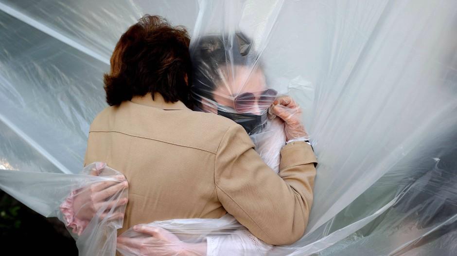 Sicher ist sicher: Eine Frau umarmt in New York ihre Großmutter durch eine Plastikfolie.