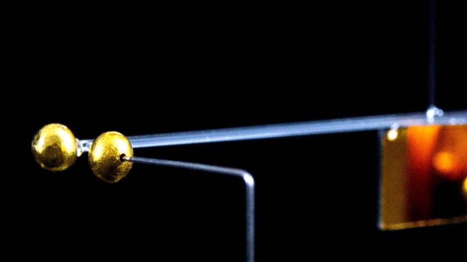 Abgeschirmt: Diese Torsionswaage misst die schwache Anziehungskraft zwischen den Millimeter großen Goldkügelchen. Die beiden Testmassen sitzen am Ende eines drehbar aufgehängten Glasstabes.
