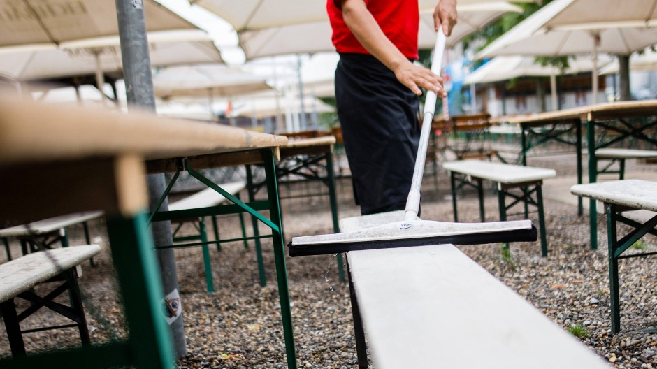 Harte Arbeit, geringer Lohn: Ein Kellner putzt die Sitzbänke in einem Biergarten.