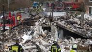 Nur noch Schutt und Asche: Feuerwehrkräfte stehen vor dem zerstörten Gebäude.