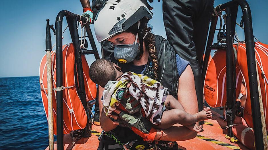 """Die Helferin eines Teams des rettungsschiffes """"Ocean Viking"""" hält ein Kind in den Armen, das zuvor aus einem überfüllten Boot gerettet wurde."""