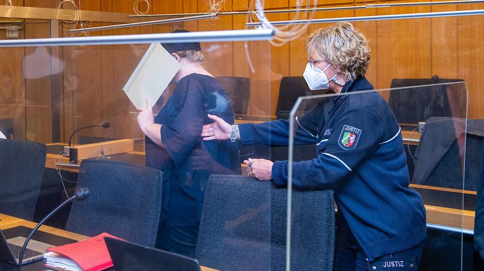 Zu Beginn des Prozesses im Missbrauchskomplex Münster wird die Mutter (l) eines Opfers von einer Justizbeamtin in den Saal des Landgerichts geführt.
