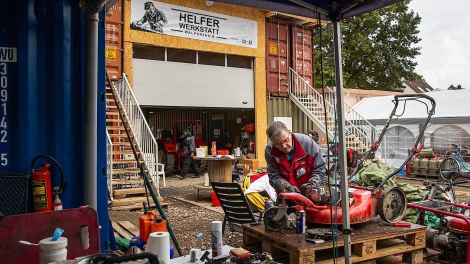 In einer Helferwerkstatt in Bad Neuenahr-Ahrweiler.reparieren Ehrenamtliche am 11. Oktober 2021 Fahrzeuge und Geräte von Betroffenen der Flut.