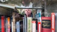 Ein Mann sucht sich Bücher in einem öffentlichen Bücherschrank in Sachsenhausen an dem Schweizer Platz aus.