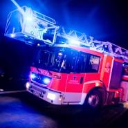 Ein Drehleiterwagen der Feuerwehr fährt mit Blaulicht an einer Unfallstelle vorbei (Archivbild).