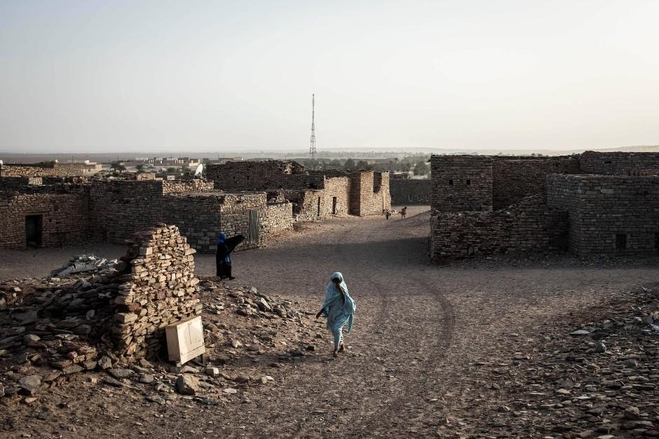 Eine Frau geht zwischen den baufälligen Häusern von Tichitt umher. Die mittelalterliche Handelssiedlung ist seit 1996 von der UNESCO zum Weltkulturerbe erklärt worden.