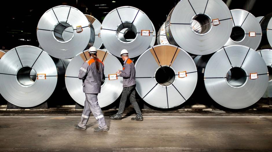 Zwei Mitarbeiter gehen vor aufgewickelten Metallbändern, sogenannten Coils, in einer Halle auf dem Gelände der Salzgitter AG entlang.