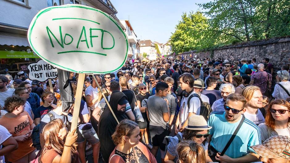 Demonstranten protestieren hinter einer Absperrung gegen eine Wahlkampfveranstaltung der AfD Hessen.