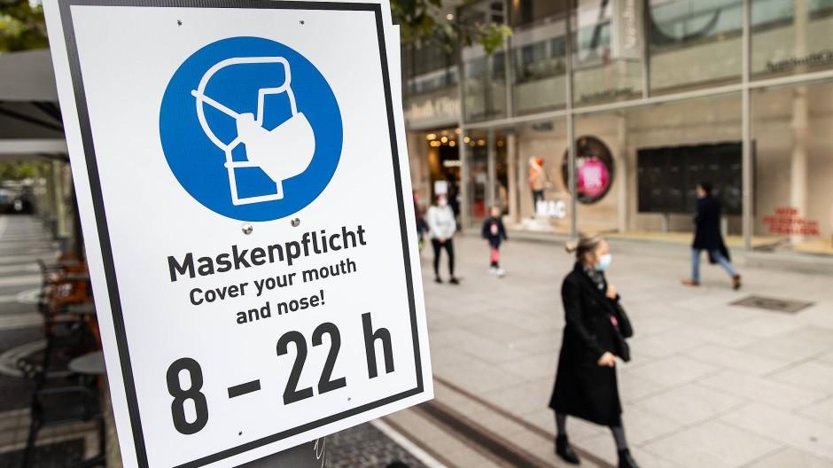 Ein Schild auf der Zeil erinnert Passanten an die Maskenpflicht.