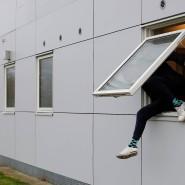 Ein Bewohner klettert aus dem Fenster seines Wohnblocks.