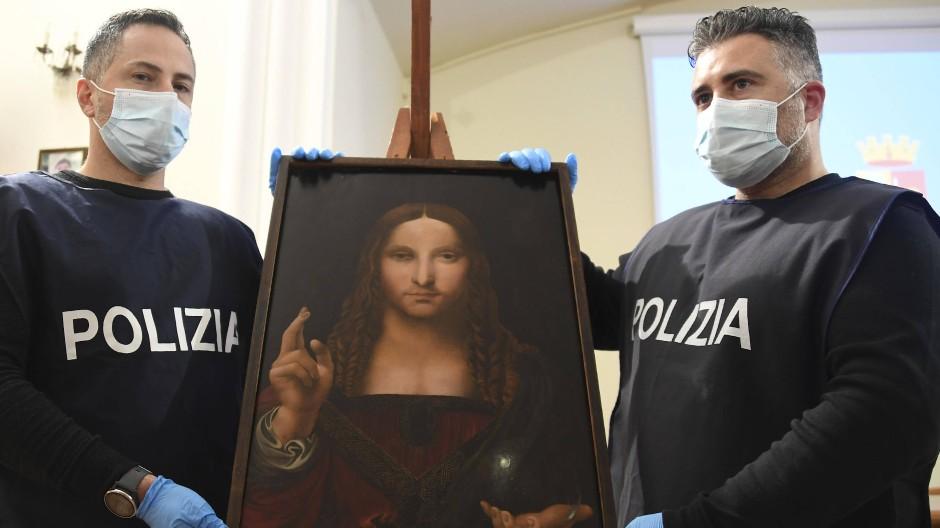 """Sichergestellt: Zwei italienische Polizisten mit dem am Montag in einer Wohnung in Neapel entdeckten """"Salvator Mundi"""""""