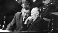 Bundesverteidigungsminister Franz Josef Strauß (l, CSU) unterhält sich am 09.11.1962 im Bundestag in Bonn mit Bundeskanzler Konrad Adenauer (CDU) während einer Debatte.
