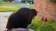 Eine ehemalige Mitarbeiterin des Gerichts legt am Tatort Blumen nieder.