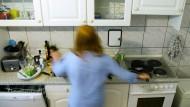 Eine junge Frau hantiert in einer Küche
