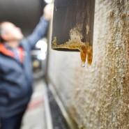 Ein Gebäudemanager steht vor einer feuchten, sanierungsbedürftigen Mauer (Symbolbild).
