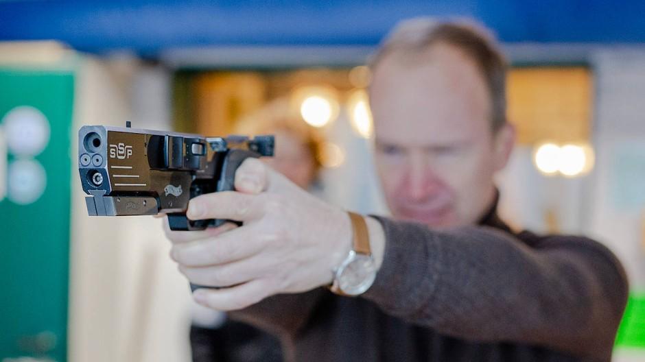 """Reinhard Müller kurz bevor er mit der Walther-Pistole einen Schuss im """"Schützenverein Bad Vilbel 1898 e.V."""" abfeuert. Sein kleiner Sohn schaut ihm dabei zu."""