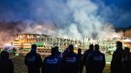 Die Mitarbeiter einer Schreinerei stehen am frühen Morgen vor den rauchenden Trümmern ihres Betriebes.