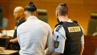 Einer von elf Angeklagten wird vor dem Prozessbeginn von einem Justizbeamten in einen Gerichtssaal im Landgericht gebracht.