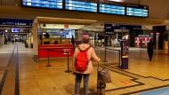 Eine Reisende am frühen Morgen in der Eingangshalle des Kölner Hauptbahnhofs.