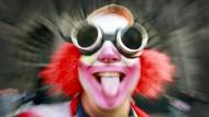 Ein als Clown verkleideter Karnevalist streckt die Zunge heraus