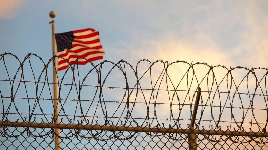 Eine US-amerikanische Flagge weht hinter einem Stacheldrahtzaun im Wind. (Symbolbild)