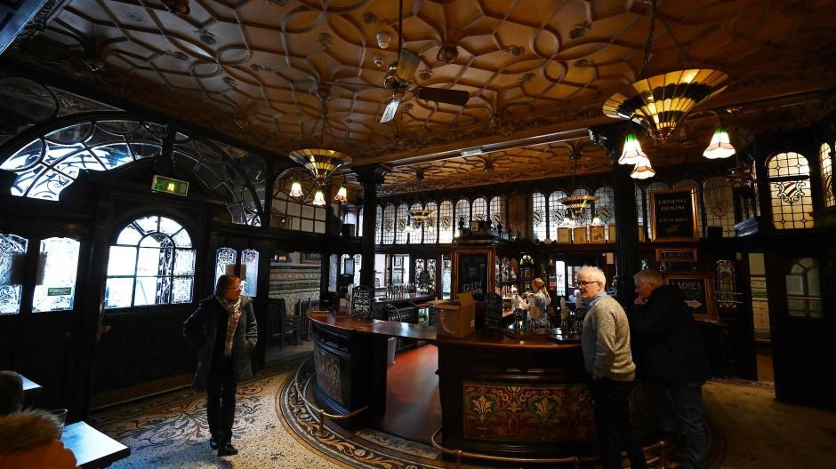 Mosaik und dunkles Holz: Besucher an der Bar in der Eingangshalle