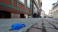 Ein blauer Einweghandschuh liegt in Wolfenbüttel vor einem Haus, wo am Vorabend neun Geburtstagsgäste mit einem abgebrochenen Balkon im Innenhof in die Tiefe gestürzt waren.