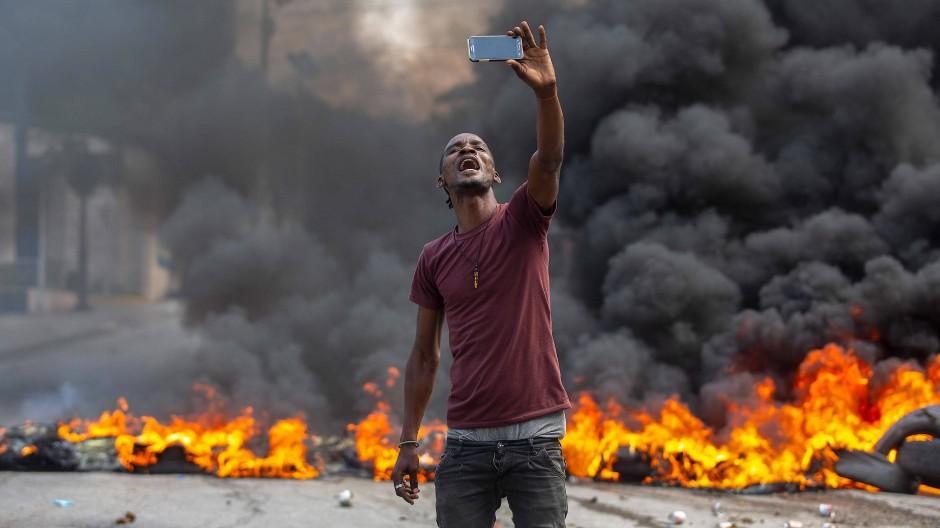 Selfie vor einer brennenden Barrikade: Zwei Tage nach der Entführung der Missionare streiken Arbeiter wegen der prekären Sicherheitslage im Land.