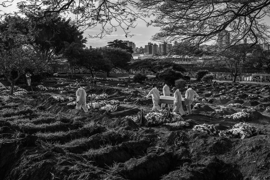 Friedhofsarbeiter in Schutzkleidung begraben ein Covid-19-Opfer auf dem Friedhof Sao Luiz am südlichen Stadtrand von São Paulo. Auf diesem Friedhof wurden seit Beginn der Corona-Krise Tausende Leichen bestattet.